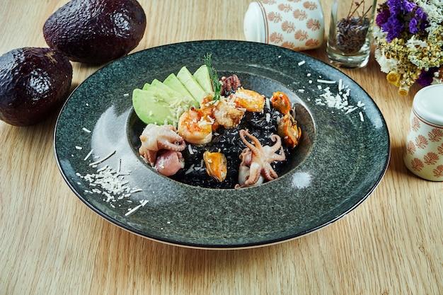 Schwarzes reisrisotto mit parmesan, avocado und meeresfrüchten: garnelen, tintenfischbaby und muscheln in einer schüssel auf einem holztisch. italienisches essen. gourmet essen. gesundes essen