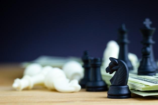 Schwarzes schach steht auf dollarbanknoten und holztische mit weißem schach fällt.