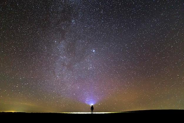 Schwarzes schattenbild des mannes mit haupttaschenlampe auf grasartigem feld unter sternenklarem himmel des schönen dunklen sommers.