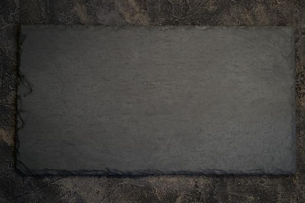 Schwarzes schieferbrett auf dunklem steinhintergrund. draufsicht mit kopie s
