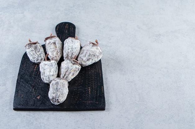 Schwarzes schneidebrett aus getrockneten kakifrüchten auf steinhintergrund.