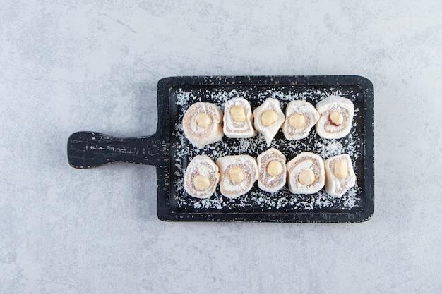 Schwarzes schneidebrett mit köstlichen leckereien mit nüssen auf stein.