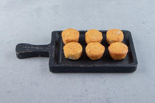 Schwarzes schneidebrett von süßen minikuchen auf steinhintergrund. foto in hoher qualität