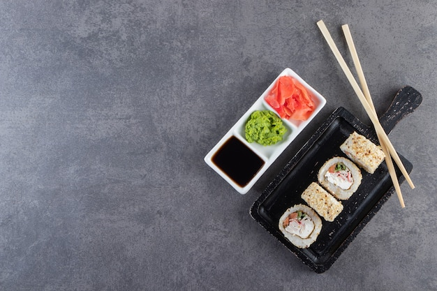 Schwarzes schneidebrett von sushirollen mit sesam auf steinhintergrund.