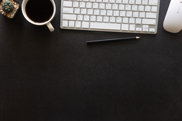 Schwarzes schreibtischbüro mit laptop, smartphone und anderen arbeitsmaterialien mit tasse kaffee. draufsicht mit kopienraum für die eingabe des textes. designer-arbeitsplatz auf schreibtischtisch wesentliche elemente auf flacher lage.