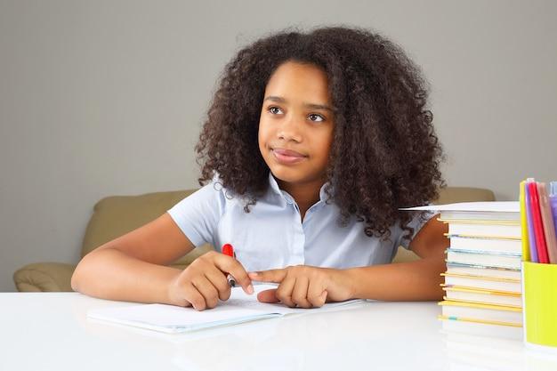 Schwarzes schulmädchen schreibt in ein notizbuch und macht hausaufgaben