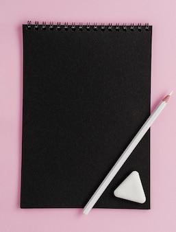 Schwarzes skizzenbuchmodell, weißer bleistift und radiergummi auf rosa hintergrund.