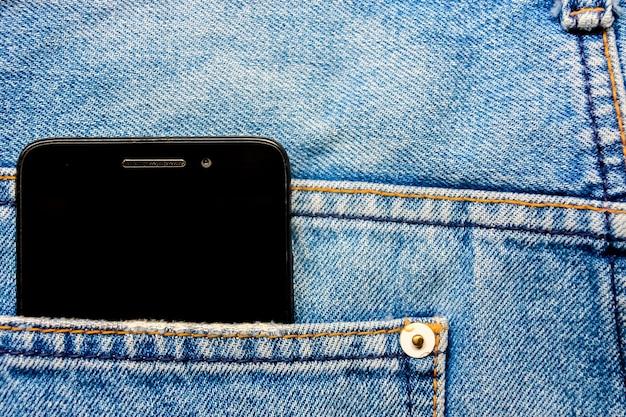 Schwarzes smart-handy in der hintergrund-jeans-hintergrundbeschaffenheit der blauen jeans zurück.