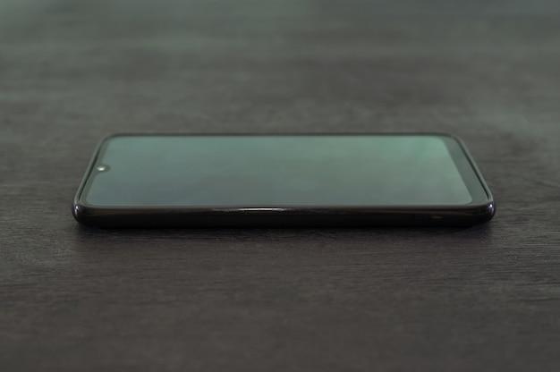 Schwarzes smartphone auf einem schwarzen tisch.