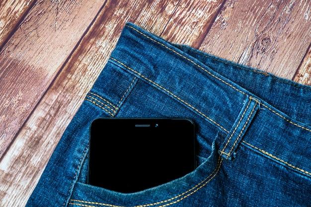 Schwarzes smartphone, das aus seiner jeanstasche herausragt
