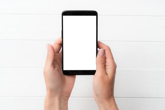 Schwarzes smartphone-modell in der hand für ihr design auf weißem tischhintergrund