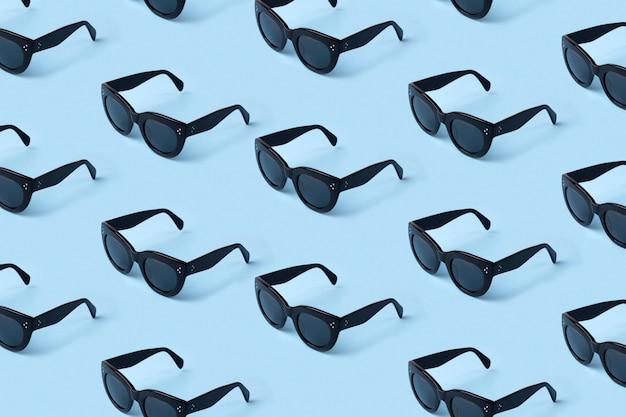 Schwarzes sonnenbrillenmuster auf pastellblau.