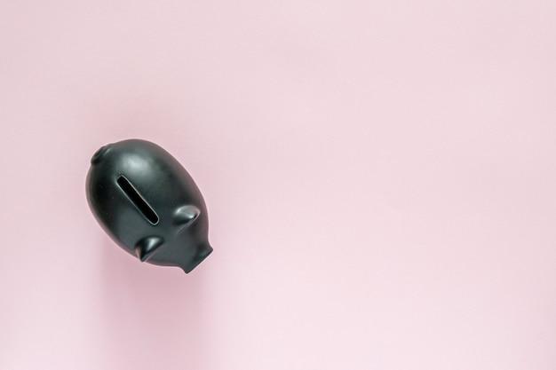 Schwarzes sparschwein über einem rosa tisch. geld sparen konzept