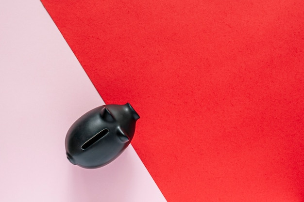 Schwarzes sparschwein über einem rosa und roten tisch. geld sparen konzept