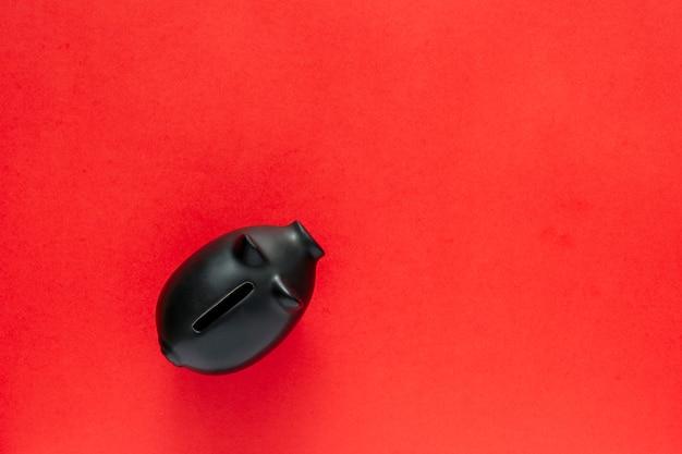Schwarzes sparschwein über einem roten tisch. geld sparen konzept