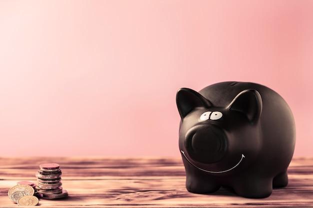 Schwarzes sparschwein und münzen auf einem holztisch auf rosafarbenem hintergrund. platz kopieren.