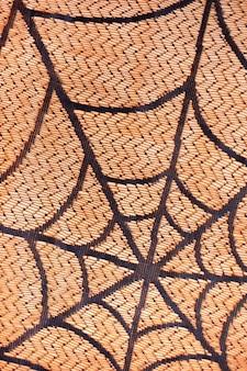 Schwarzes spinnennetz auf orange hintergrund. vertikale.