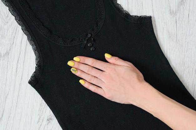 Schwarzes spitzen-trägershirt und weibliche hand. einzelheiten, nahaufnahme. modisches konzept