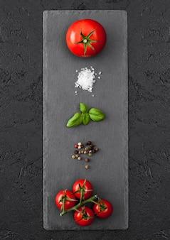 Schwarzes steinbrett mit tomaten, salz und pfeffer und basilikum auf schwarzem tisch.