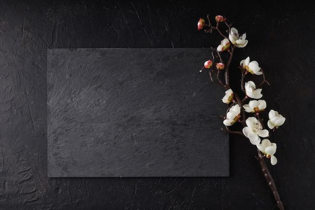 Schwarzes steintablett mit sakura auf schwarz