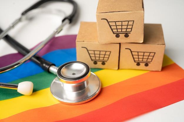 Schwarzes stethoskop auf regenbogenflagge mit online-shopping-box, symbol des lgbt-stolzmonats, feiert jährlich im juni sozial, symbol für schwule, lesben, bisexuelle, transgender, menschenrechte und frieden.
