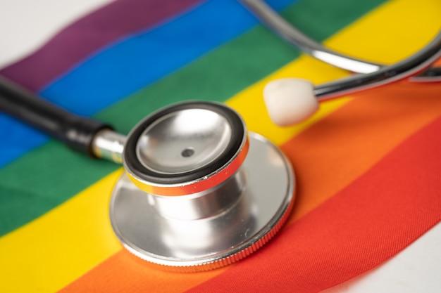 Schwarzes stethoskop auf regenbogenflaggenhintergrund, symbol des lgbt-stolzmonats, feiert jährlich im juni sozial, symbol für schwule, lesben, bisexuelle, transgender, menschenrechte und frieden.