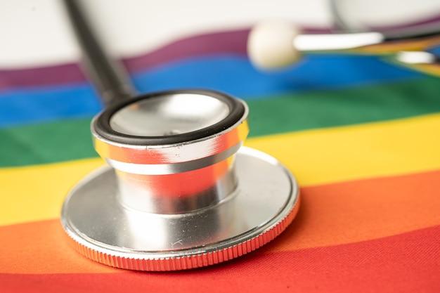 Schwarzes stethoskop auf regenbogenflaggenhintergrundsymbol des lgbt-stolzmonats