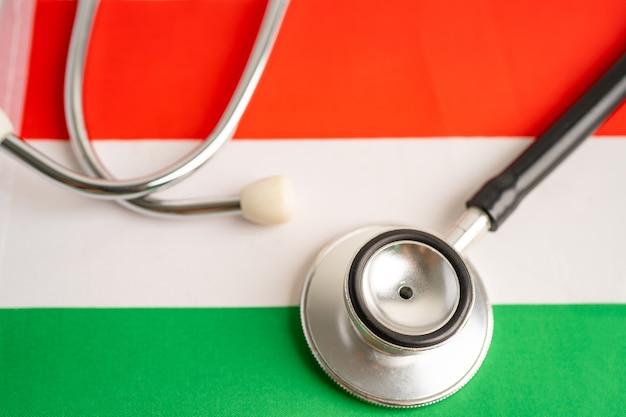 Schwarzes stethoskop auf ungarischem flaggenhintergrund, geschäfts- und finanzkonzept.