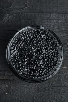 Schwarzes störkaviarglas, auf schwarzem holztisch, draufsicht flach gelegt