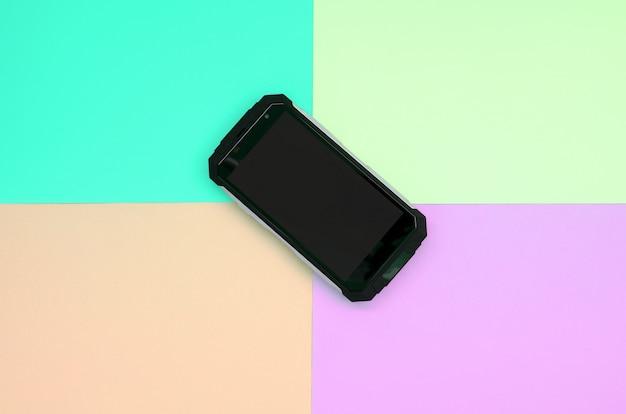 Schwarzes stoßfestes smartphone liegt auf einem pastellfarbenen pappers