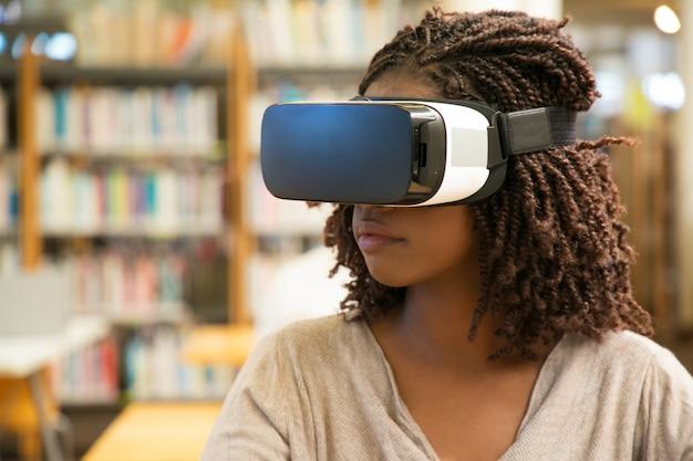Schwarzes studentinmädchen, das vr-gläser für arbeit verwendet