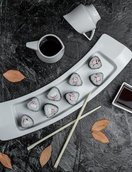 Schwarzes sushi mit soße in der platte