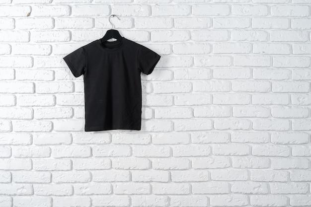Schwarzes t-shirt, das an einem aufhänger gegen backsteinmauer hängt