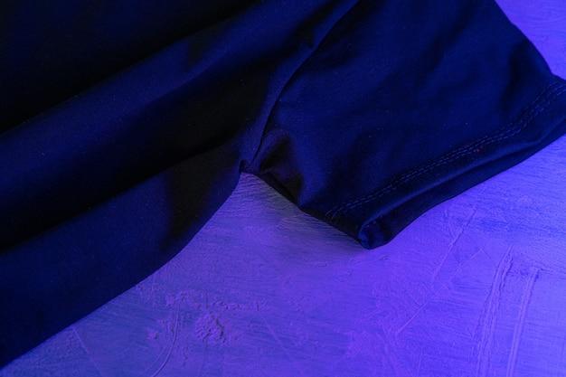 Schwarzes t-shirt im neonlicht schließen oben auf einem tisch