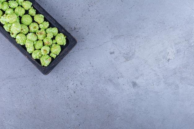 Schwarzes tablett, das einen knusprigen haufen kandierten popcorns auf marmoroberfläche hält