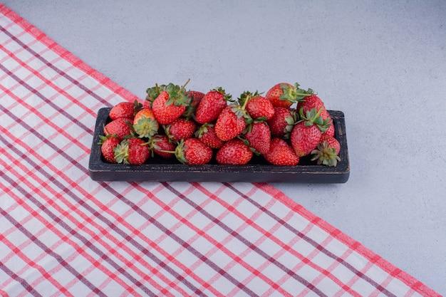 Schwarzes tablett mit einer portion frischer erdbeeren auf tischdecke auf marmorhintergrund.
