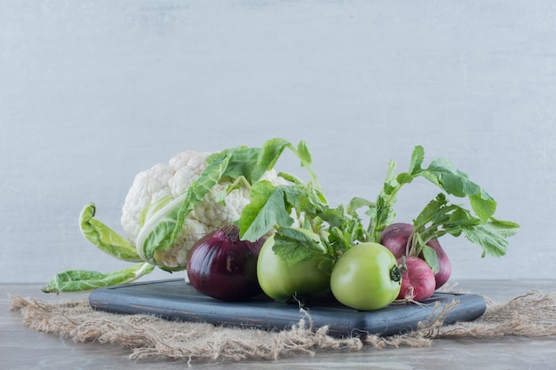 Schwarzes tablett mit roten zwiebeln, blumenkohl, grüner tomate, rüben und rübenblättern auf marmor.