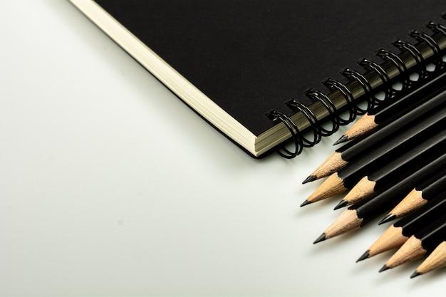 Schwarzes tagebuchbuch und ein bleistift auf grauem schreibtischhintergrund mit kopienraum
