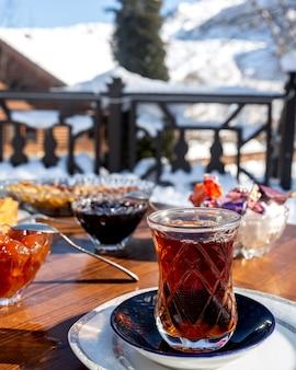 Schwarzes te mit schwarzen und weißen kirschmarmeladenbonbons und zucker auf tisch