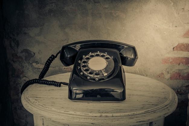 Schwarzes telefon der weinlese auf altem wandhintergrund
