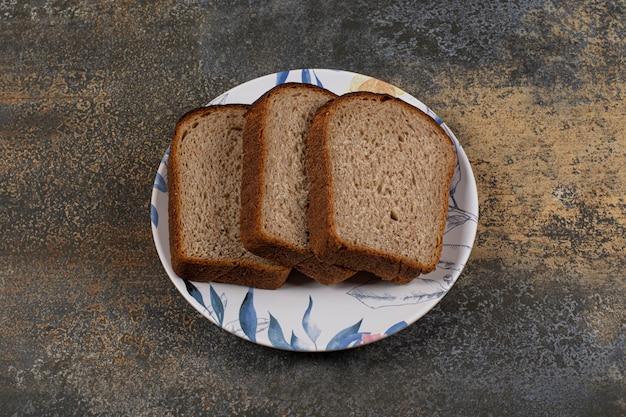 Schwarzes toastbrot auf buntem teller