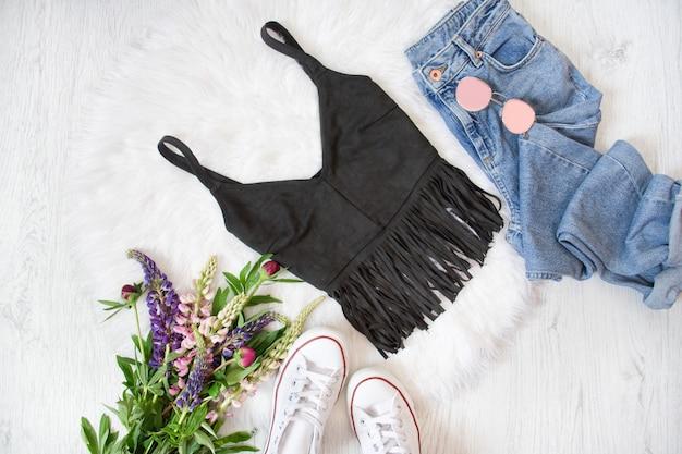 Schwarzes top mit fransen, blue jeans, weißen turnschuhen. strauß wilder blumen. modisches konzept