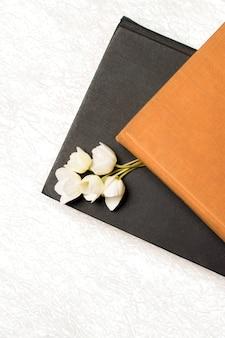 Schwarzes und braunes buch mit blumen auf einem weiß