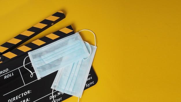Schwarzes und gelbes clapper board oder filmschiefer mit gesichtsmaske. es wird in der videoproduktion und in der kinoindustrie auf gelbem hintergrund verwendet.