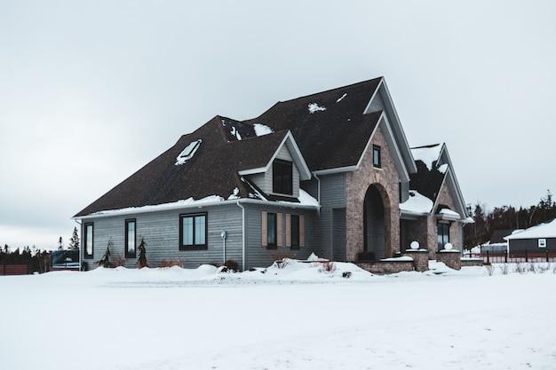 Schwarzes und graues haus im winter