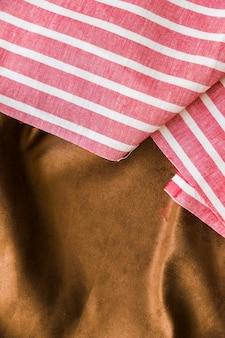 Schwarzes und rotes gestreiftes mustergewebe über dem glatten braunen textil