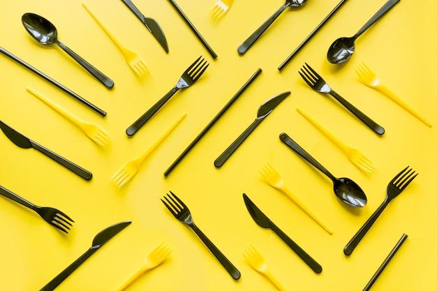 Schwarzes wegwerfmesser und gabeln des picknicks auf gelb.