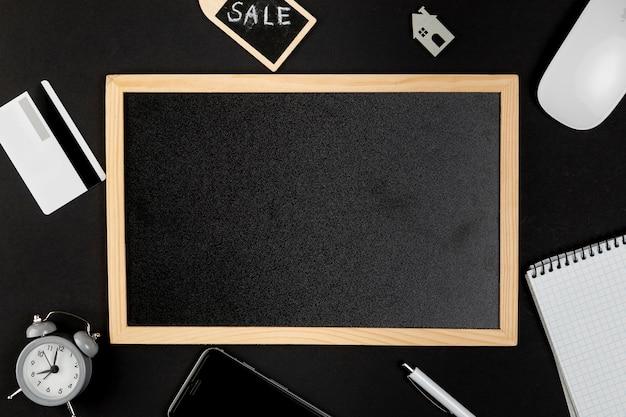Schwarzes whiteboard mit schreibtischsachen herum