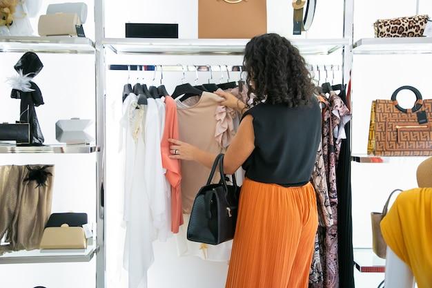 Schwarzhaarige frau, die kleidung wählt und kleider und hemden auf gestell durchsucht. rückansicht. modegeschäft oder einzelhandelskonzept