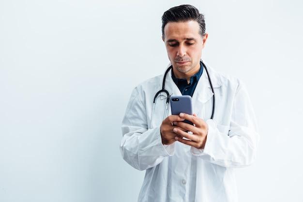 Schwarzhaariger arzt, der weißen kittel und stethoskop trägt und sein handy auf weißem hintergrund betrachtet.